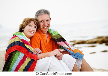 Happy mature couple sitting on the beach