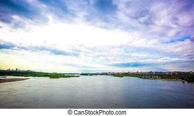Timelapse of moving Of clouds on the coastline in the sky.View on Novosibirsk from the bridge