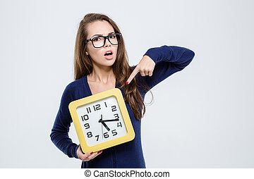 Woman pointing finger on wall clock - Portrait of a young...