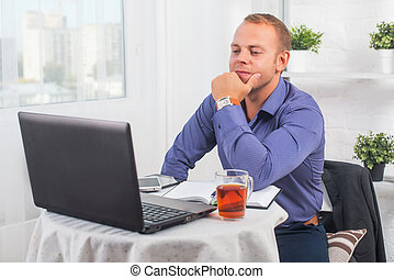 Businessman working in office, sitting at table with a laptop