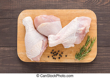 Raw chicken drumsticks on cutting board on wooden background