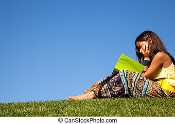 Reading at the park - young female child at the park reading...