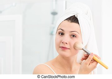 Female applying face powder - Image of female applying face...