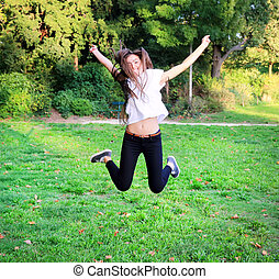 Beautiful happy young teen girl jumping high in the park