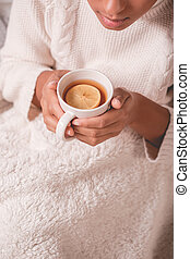 Girl sitting under blanket - Girl with tea cup sitting under...