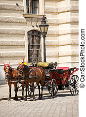 Horsedrawn carriage on the platz by the Hofburg Palace,...