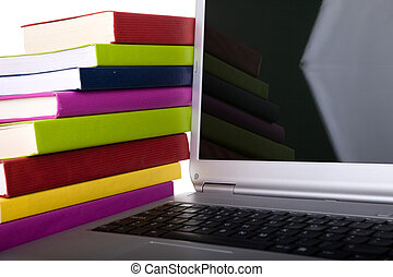 E-Book - Colorful books next to a modern laptop