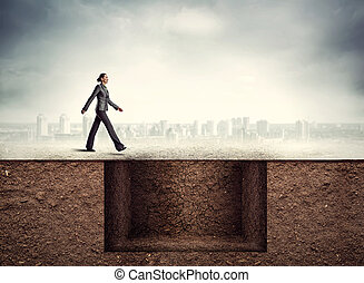Woman near a deep pit - Businesswoman going to the trap
