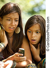 sms surprise - two young sisters reading a new sms at the...