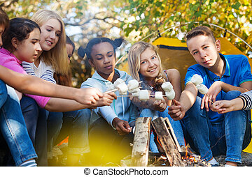 Friends hold marshmallow sticks near bonfire - Group of...
