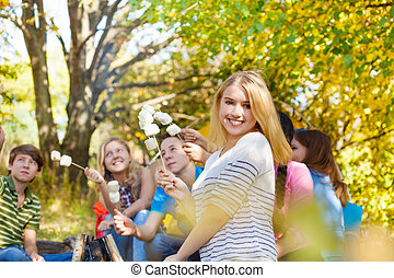Girl and friends with marshmallow sticks sitting near...