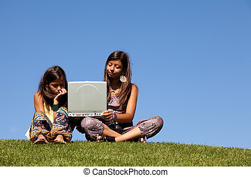 wireless internet - two young sisters using the internet at...