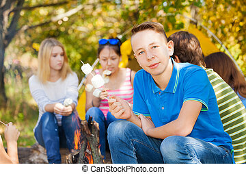 Boy and friends hold marshmallow sitting near tent - Boy and...