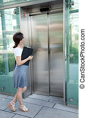 waiting for the elevator - modern businesswoman waiting for...
