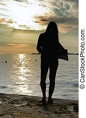 Silhouette woman and sunset on the beach - Silhouette woman...