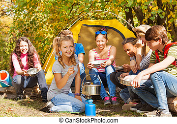 Girl cooks soup in the pot near yellow tent with friends...