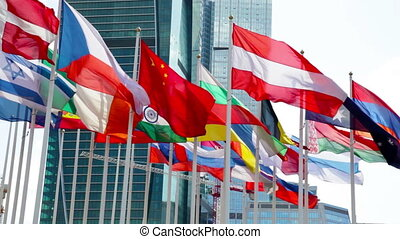 Flags waving near modern office building - Cloudy view at...
