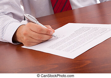 Signing a contract - businessman at the office signing a...
