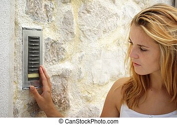 Woman using house intercom, outdoor - Woman using house...