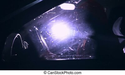 man sits in the car at night and touches of blue light goes...
