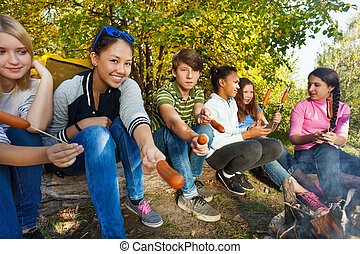 Teens grilling sausages sitting near yellow tent on campsite...