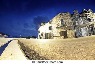 Old street of stone houses by the sea at night, Croatia