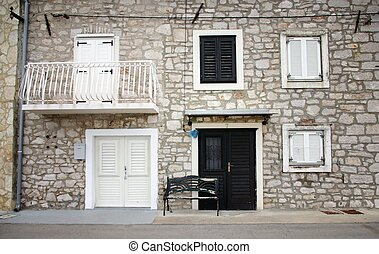 Old stone house with shutters in front view