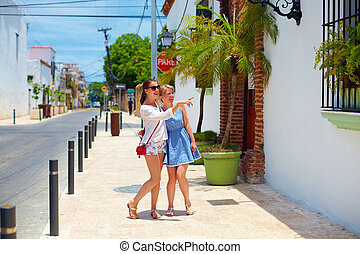 happy young girls, tourists walking on streets in city tour,...