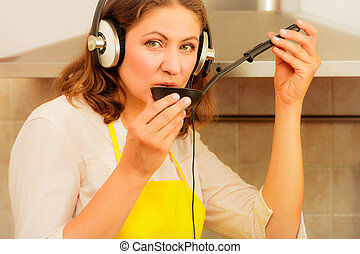Housewife with earphones in kitchen - Cooking and preparing...