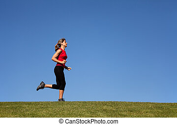 woman running in the green grass with copyspace