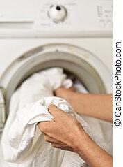 young man doing laundry - closeup of a young man introducing...