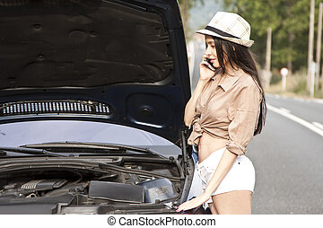 girl with broken car on the road