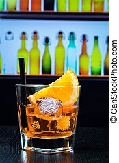 glass of spritz aperitif aperol cocktail with orange slices and ice cubes on bar table, disco lounge bar atmosphere background