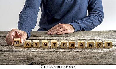 Front view of a man assembling the word Maintenance