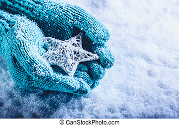 Female hands in light teal knitted mittens with entwined...