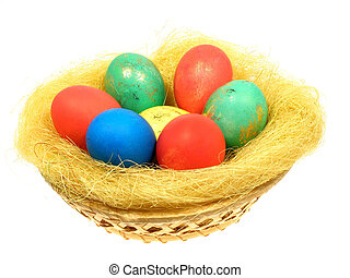 Colored eggs in a wicker basket from vines within the straw