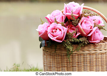 bouquet of pink roses in bamboo basket