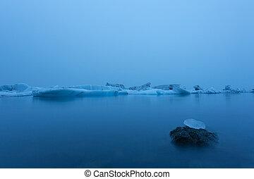 Iceberg in lagoon at midnight. Long exposure