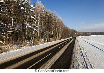 winter road . snow - a small country road passes in a field...