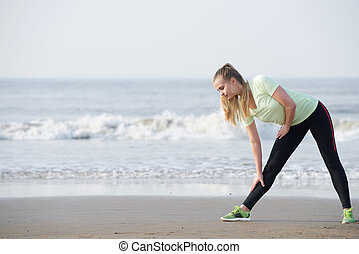 Sporty young woman bend down stretching at the beach - Full...