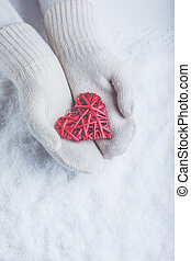 Female hands in white knitted mittens with entwined vintage...