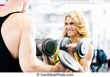 Man and woman in fitness gym lifting dumbbells