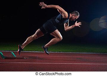 Sprinter leaving starting blocks on the running track...