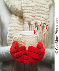 Woman hands in woolen red gloves holding cozy mug with hot...