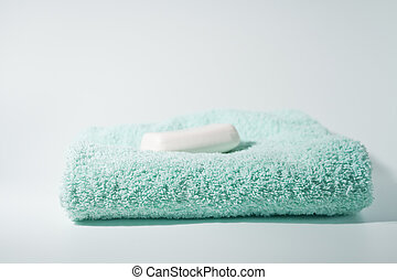 bar of soap and blue green towel - bar of white soap on top...