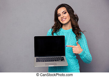 Woman pointing finger on blank laptop computer screen -...