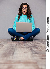 Surprised woman sitting on the floor with laptop - Portrait...