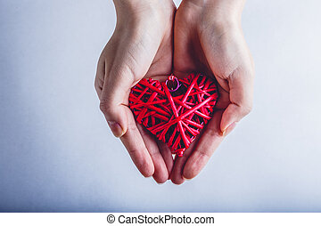Female hands with a entwined vintage romantic red heart on a...