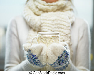 Woman hands in white and blue mittens holding a cozy knitted...