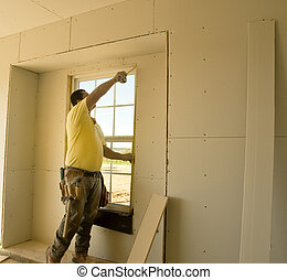 Man Measuring Window - Man measuring window to sheetrock...